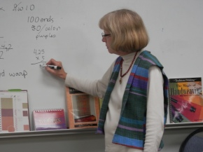 Linda, wearing the striped vest, led the group through the math calculations.