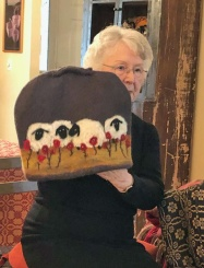 Betty's tea cozy is made of New Zealand opossum blended with wool to illustrate her love of weaving and wool. The sheep are needle felted, another one of her fiber-related favorites.