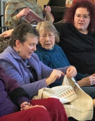 Kathy, Jacque and Amber admire Jackie's tea towel woven in 8-shaft rosepath--a loving tribute to her grandmother and her own love of gardening.