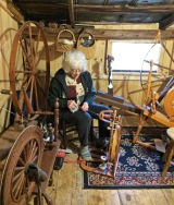 Diane, a former member, spins in a room full of spinning wheels